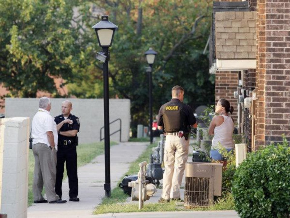 Edmond police stand outside an apartment being searched as they execute search warrants at Rolling Green Apartments, 400 E. Danforth in Edmond on Wednesday.Photo by Paul B. Southerland, The Oklahoman ORG XMIT: KOD PAUL B. SOUTHERLAND - PAUL B. SOUTHERLAND