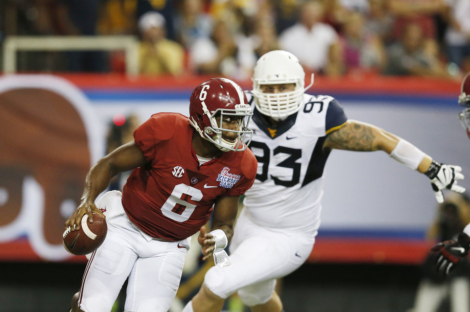 Photo - Alabama quarterback Blake Sims (6) scrambles away from West Virginia defensive lineman Kyle Rose (93) during the first half of an NCAA college football game Saturday, Aug. 30, 2014, in Atlanta.  (AP Photo/Bryn Anderson)