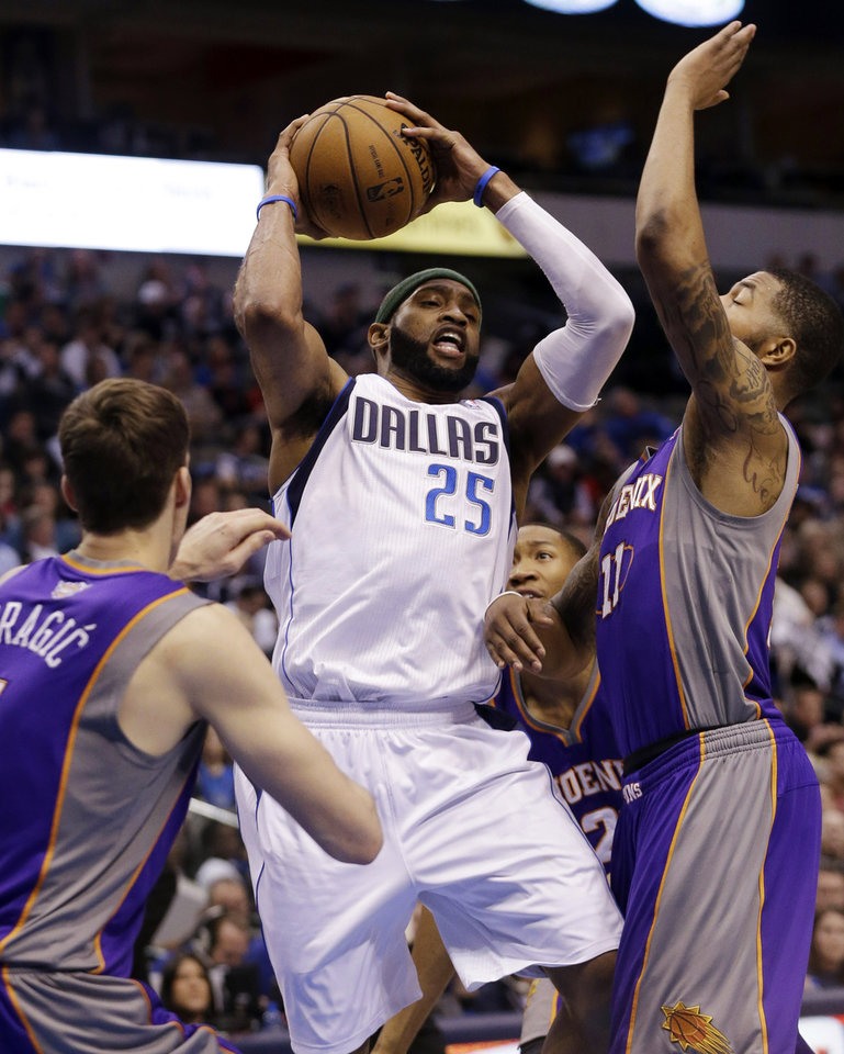 Photo - Dallas Mavericks' Vince Carter (25) drives against Phoenix Suns' Markieff Morris (11), Wesley Johnson (2)  and Goran Dragic (1) during the first half of an NBA basketball game, Wednesday, April 10, 2013, in Dallas. (AP Photo/LM Otero)