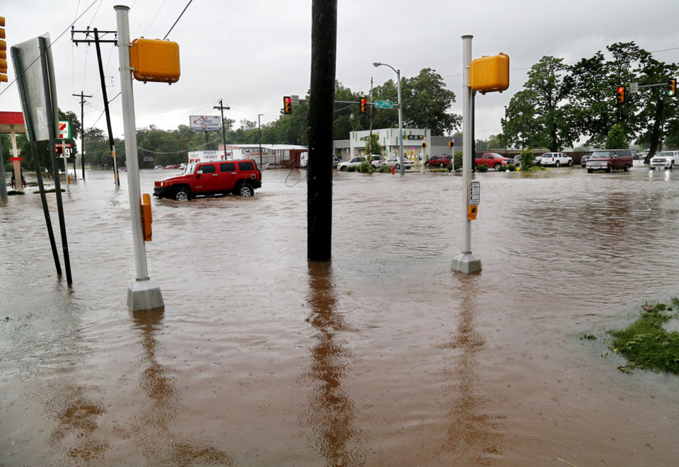 Photo - A vehicle attempts to cross a flooded street in Oklahoma City following severe weather last June. Firefighters said they assisted four people to safety in the deep water that flooded this intersection at SW 29 and May. [Jim Beckel/The Oklahoman file photo]