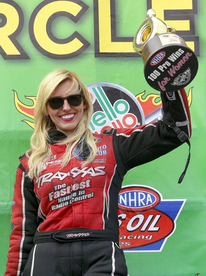 Photo - Funny Car driver Courtney Force raises one of her trophies for being the 100th professional win for women drivers in the NHRA after defeating Cruz Pedregon in the finals at Heartland Park in Topeka, Kan., on Sunday May 25, 2014. (AP Photo/The Topeka Capital Journal, Chris Neal)