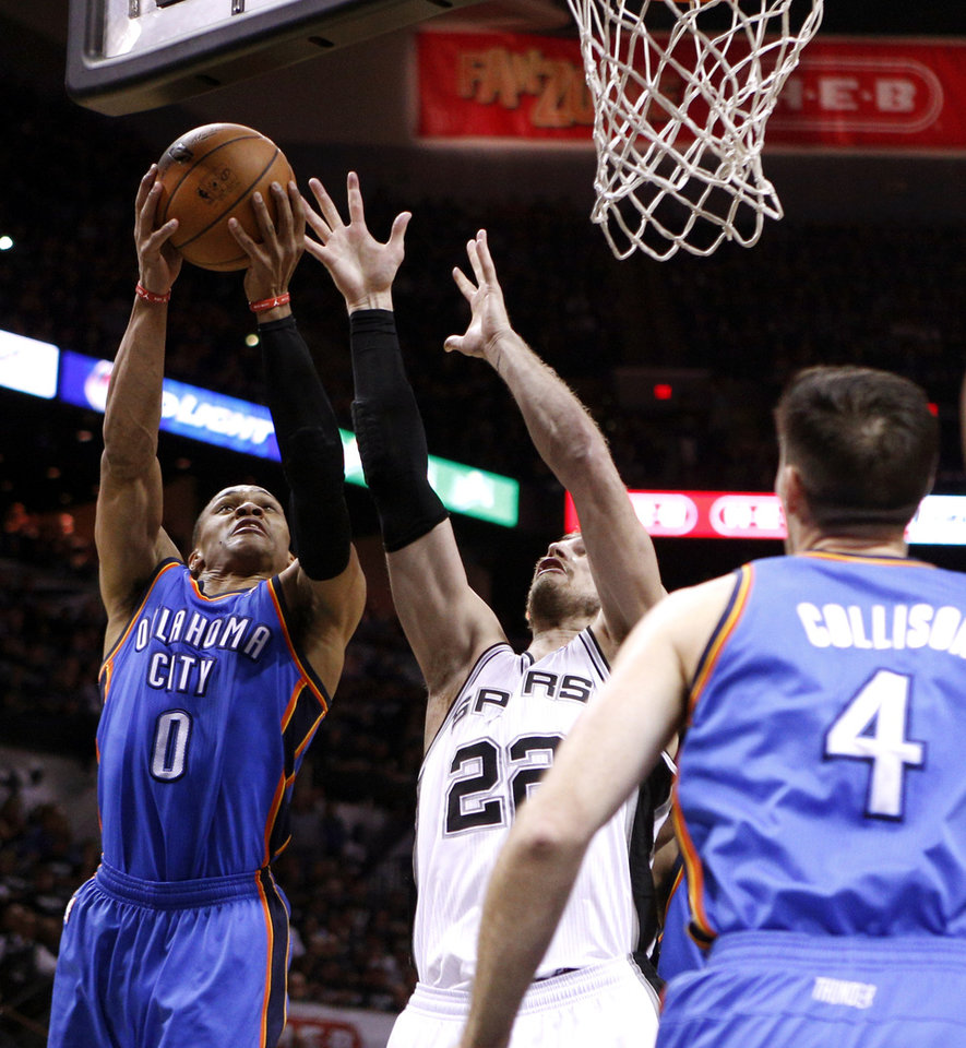 Photo - Oklahoma City's Russell Westbrook (0) leaps for the ball beside San Antonio's Tiago Splitter (22) during Game 1 of the Western Conference Finals in the NBA playoffs between the Oklahoma City Thunder and the San Antonio Spurs at the AT&T Center in San Antonio, Monday, May 19, 2014. Photo by Sarah Phipps, The Oklahoman