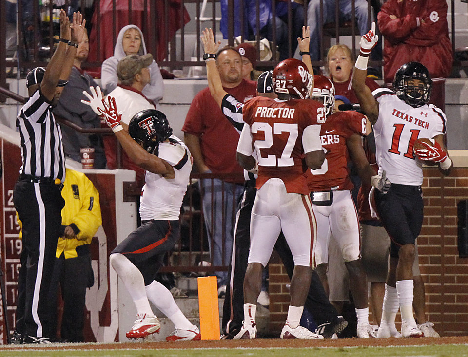 Photo - Texas Tech's Brant Costilla (12) celebrates a touchdown in front of Oklahoma's Sam Proctor (27) and Demontre Hurst (6) during the college football game between the University of Oklahoma Sooners (OU) and Texas Tech University Red Raiders (TTU) at the Gaylord Family-Oklahoma Memorial Stadium on Saturday, Oct. 22, 2011. in Norman, Okla. Photo by Chris Landsberger, The Oklahoman