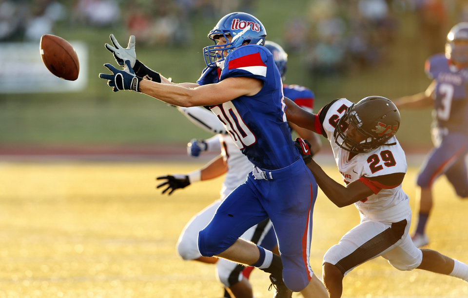 Photo - Moore's Lance Biswell (80) narrowly misses a pass in the first half guarded by Jaquar's Giavonni Knight (29) n the first half as The Moore Lions play the Westmoore Jaguars in high school football on Friday, Aug. 31, 2012 in Moore, Okla.  Photo by Steve Sisney, The Oklahoman