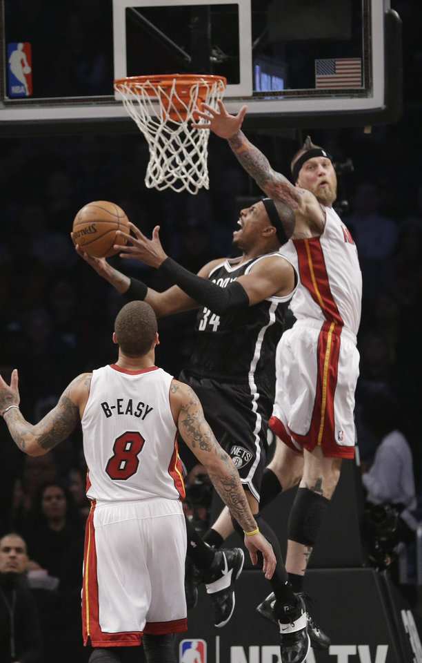 Photo - Brooklyn Nets' Paul Pierce (34) drives past Miami Heat's Chris Andersen (11) during the first half of an NBA basketball game on Friday, Jan. 10, 2014, in New York. (AP Photo/Frank Franklin II)