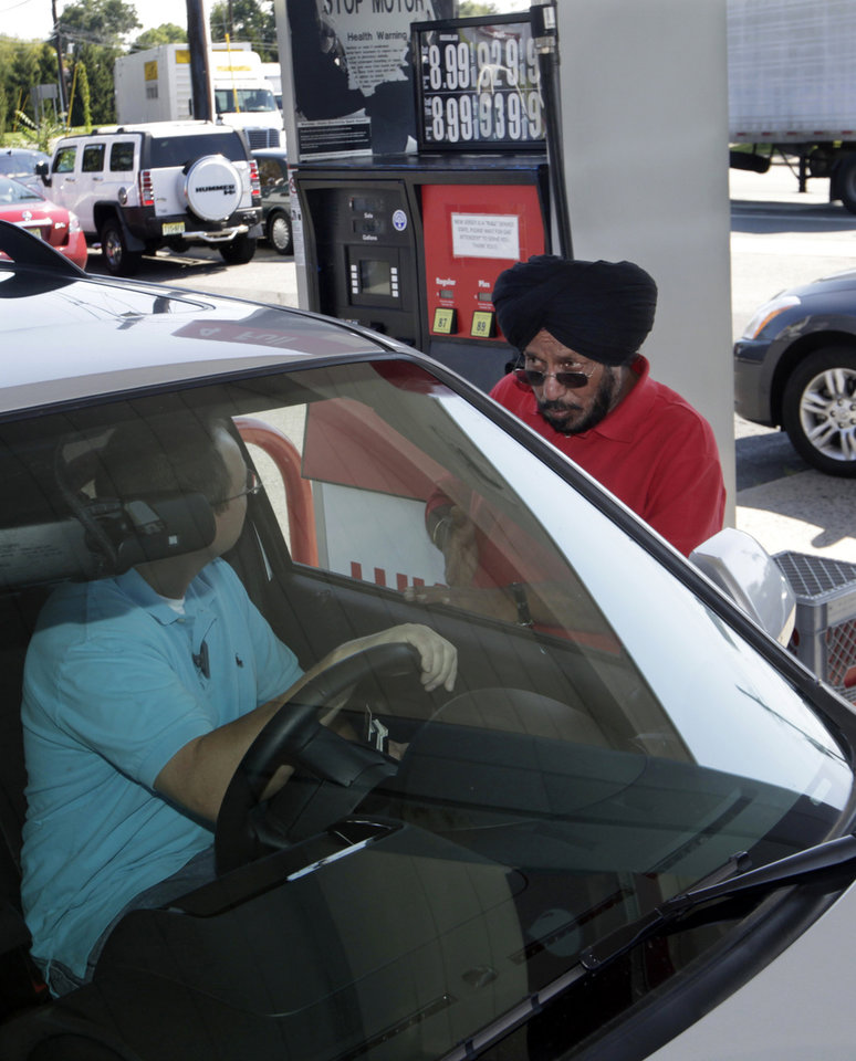 Photo -   Lukoil service station worker Harbhasan Singh explains to a customer Wednesday, Sept. 12, 2012, in South Plainfield, N.J., that as a protest to what they say are unfair pricing practices by Lukoil North America, the station has raised their gas price to more than $8 a gallon. More than 50 Lukoil gas stations in New Jersey and Pennsylvania were jacking up prices to more than $8 a gallon Wednesday to protest what they say are unfair pricing practices by Lukoil North America that they say leave them at a competitive disadvantage. (AP Photo/Mel Evans)