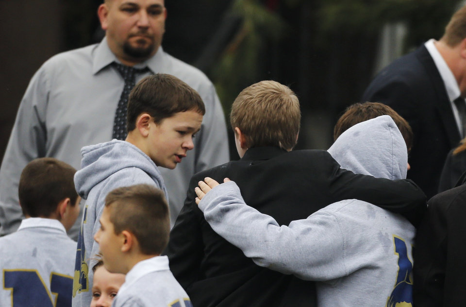 Photo - Studens embrace while wearing Newtown school shirts outside the funeral for six-year-old student shooting victim Jack Pinto in Newtown, Conn., Monday, Dec. 17, 2012. A gunman opened fire at Sandy Hook Elementary School in the town on Friday, killing 26 people, including 20 children before killing himself. (AP Photo/Charles Krupa)