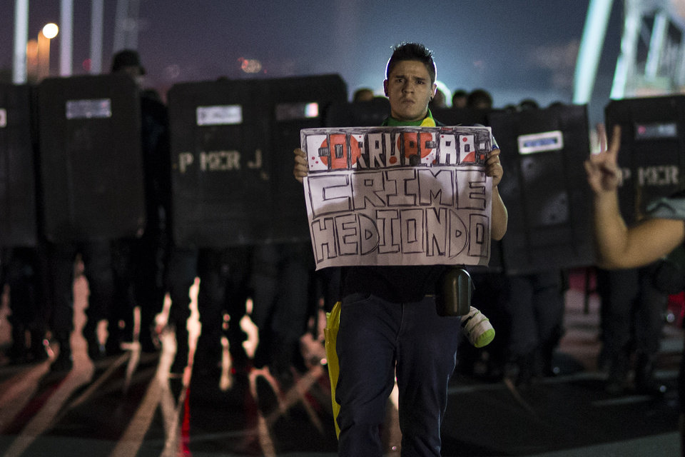 Photo - A man holds a sign that reads in Portuguese;