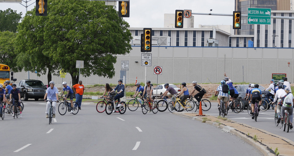 Photo - Dozens of bicyclists riding along Classen Boulevard turn left onto 16th Street, Tuesday, May 7, 2019, to highlight the need for better bike lanes, stopping at 16th and Classen Blvd. where a ghost bike memorial for Chad Epley who was killed at the intersection while riding home after work.  Photo by Doug Hoke.
