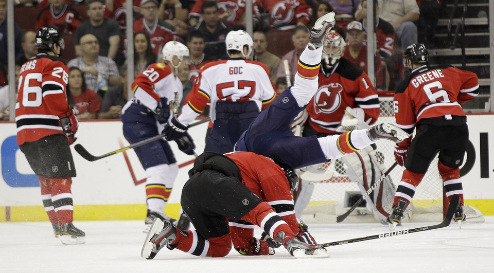 Photo -   Florida Panthers' Dmitry Kulikov, top, of Russia, flips over New Jersey Devils' Dainius Zubrus, of Lithuania, during the second period of Game 3 of a first-round NHL hockey Stanley Cup playoff series, Tuesday, April 17, 2012, in Newark, N.J. (AP Photo/Julio Cortez)
