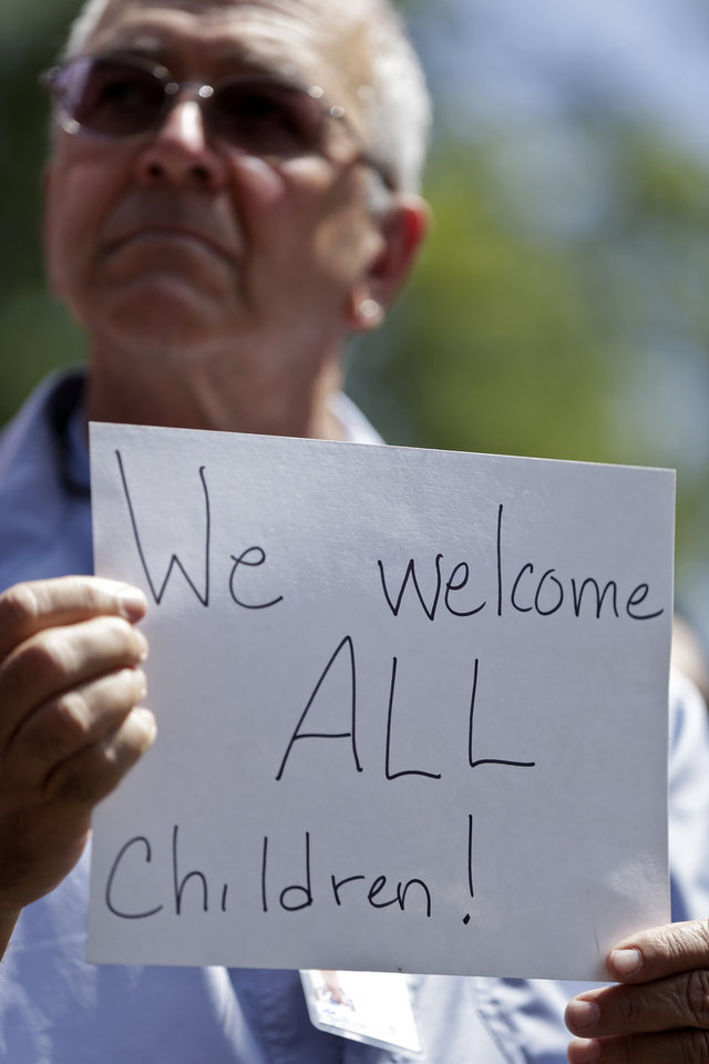 Photo - Ron Kohl holds up a sign during a rally in support of immigrants Wednesday, July 2, 2014, in San Diego. A group of about 70 people rallied in support of migrant children and families Wednesday, a day after U.S. Homeland Security buses carrying the migrants were routed away from American flag-waving protesters in Murrieta, Calif., and transported to a facility in San Diego. (AP Photo/Gregory Bull)