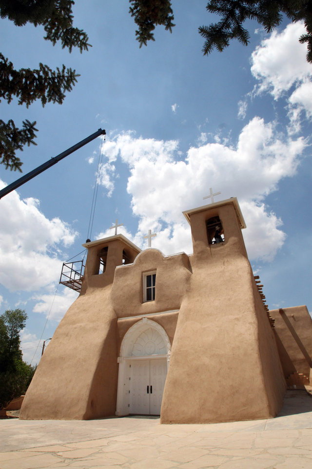 Photo - FILE - In this June 14, 2010 file photo, workers apply mud to the the San Francisco de Asis Church in Ranchos de Taos, N.M., as part of an annual ritual that has been done for nearly 200 years. The historic church was made famous by the paintings of Georgia O'Keeffe and the photographs of Ansel Adams and Paul Strand. (AP Photo/Susan Montoya Bryan)