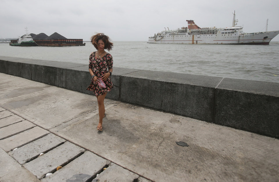 Photo - A Filipino's hair blows in the strong winds from Typhoon Koppu as she walks along the promenade where a barge and passenger boat are seen drifting close to shore by strong currents in Manila Bay, Philippines, on Monday, Oct. 19, 2015. Army, police and civilian volunteers scrambled Monday to rescue hundreds of villagers trapped in their flooded homes and on rooftops in a northern Philippine province battered by slow-moving Typhoon Koppu. (AP Photo/Aaron Favila)