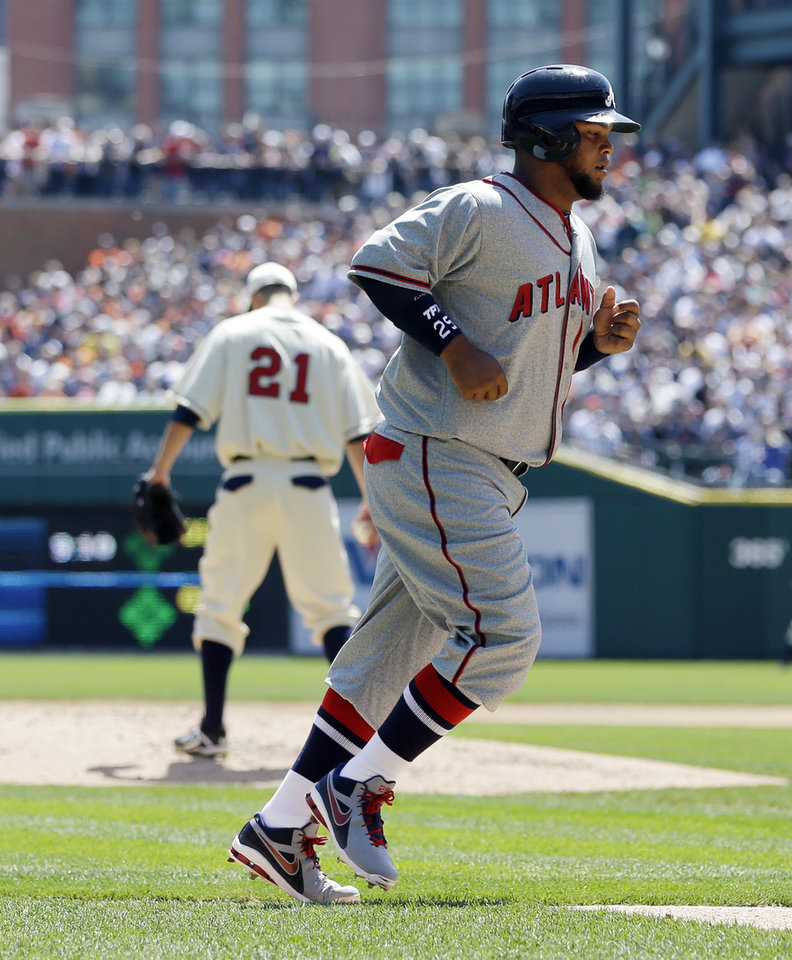 Atlanta Braves' Juan Francisco scores from third on a bases loaded walk to teammate Dan Uggla during the third inning of an interleague baseball game against the Detroit Tigers in Detroit, Saturday, April 27, 2013. In the background is Tigers starting pitcher Rick Porcello. (AP Photo/Carlos Osorio)