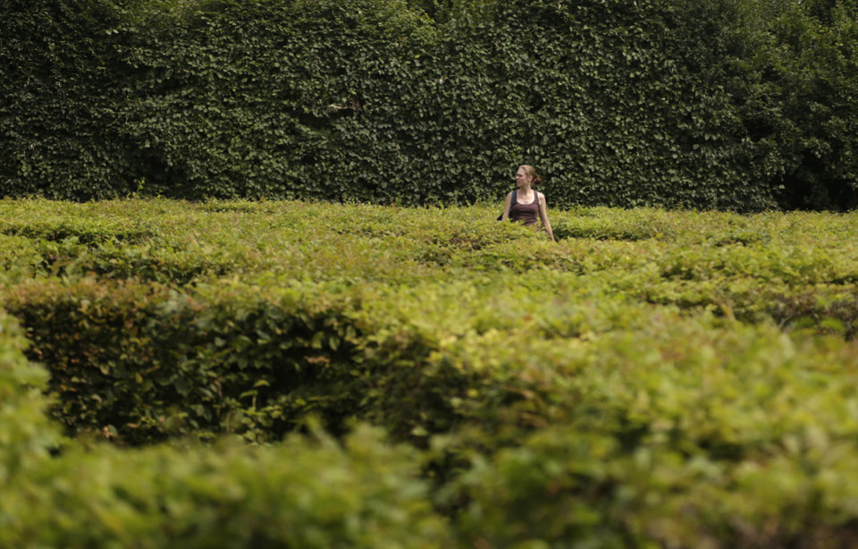 Photo - In this Aug. 7, 2014, photo, a woman walks through UNESCO's Flower Garden in city of Kromeriz, Czech Republic. With its original geometrical layout and high topiary walls, it's a rare example of an early Baroque garden style. And it's now reclaiming the unique features it had when it was completed in 1675, including labyrinths, fountains, sculptures inspired by Greek and Roman mythology, a Dutch bulb garden and citrus trees. (AP Photo/Petr David Josek)