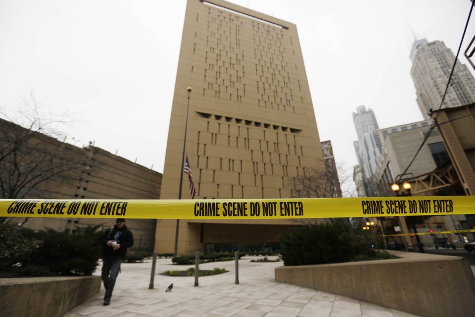 Photo - Police tape surrounds the Metropolitan Correctional Center Tuesday, Dec. 18, 2012, in Chicago. Two convicted bank robbers used a knotted rope or bed sheets to escape from the federal prison window high above downtown Chicago early Tuesday, a week after one of them made a courtroom vow of retribution, to federal judge. The escape occurred sometime between 5 a.m. and 8:45 a.m. when the inmates were discovered missing, Chicago Police Sgt. Mark Lazarro said. Hours later, what appeared to be a rope, knotted at six-foot intervals, could be seen dangling into an alley from a window of the Metropolitan Correctional Center approximately 20 stories above the ground. (AP Photo/M. Spencer Green)