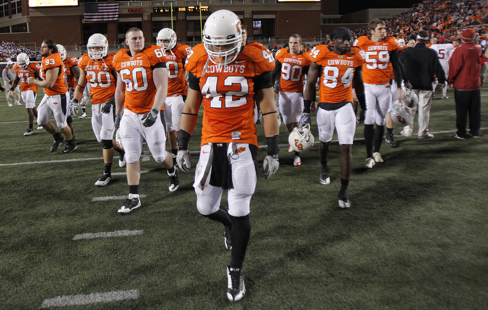 Photo - Oklahoma State's Justin Gent (42) and other Cowboys walk off the field after the 47-41 loss to Oklahoma during the Bedlam college football game between the University of Oklahoma Sooners (OU) and the Oklahoma State University Cowboys (OSU) at Boone Pickens Stadium in Stillwater, Okla., Saturday, Nov. 27, 2010. Photo by Chris Landsberger, The Oklahoman