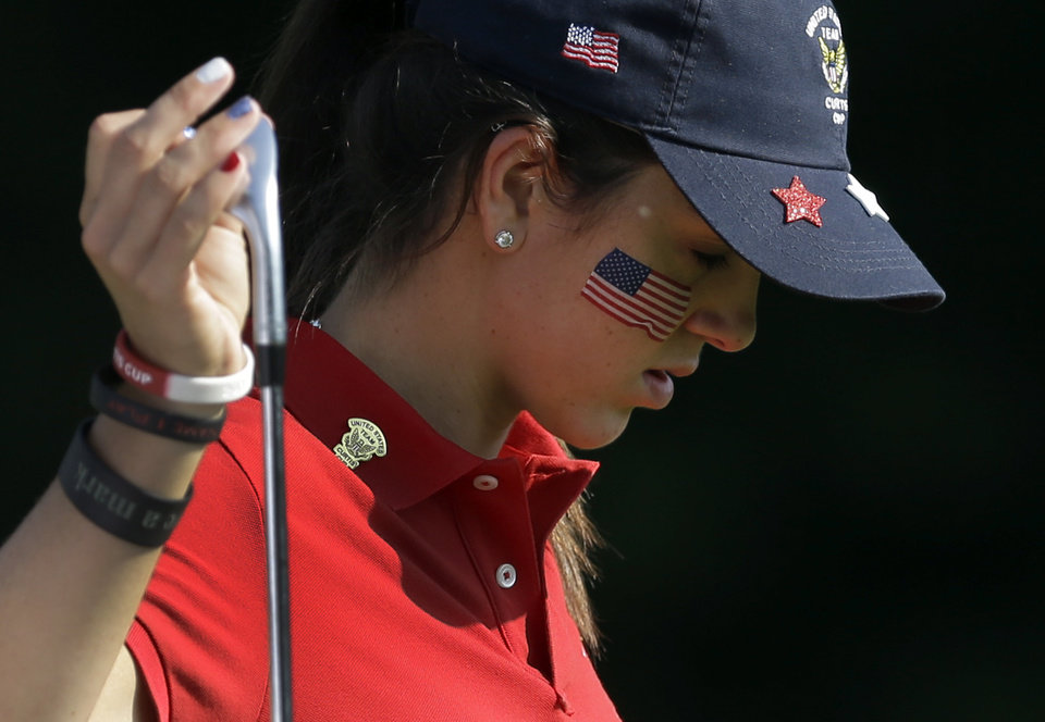 Photo - United States' Emma Talley looks down as she pulls a club out of her bag on the fifth fairway during the 38th Curtis Cup amateur golf match against Great Britain and Ireland Friday, June 6, 2014, in St. Louis. (AP Photo/Jeff Roberson)
