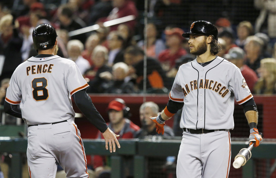 Photo - San Francisco Giants' Hunter Pence (8) celebrates after scoring against the Arizona Diamondbacks, with teammate Brandon Crawford during the sixth inning of a baseball game, Wednesday, April 2, 2014, in Phoenix. (AP Photo/Ross D. Franklin)