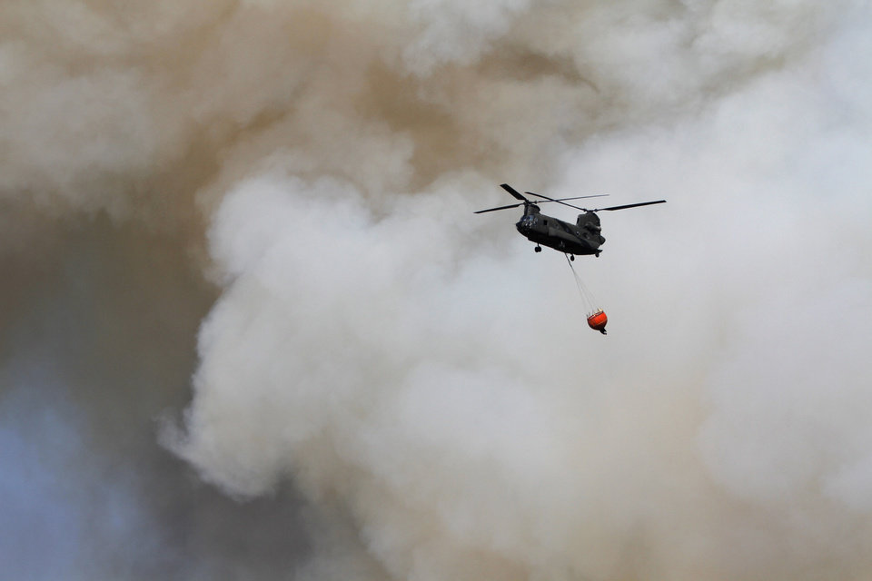 Photo - A helicopter carries water over a wildfire near NW 122nd and Midwest Blvd. in Oklahoma City, Wednesday, August 31, 2011. Photo by Bryan Terry, The Oklahoman