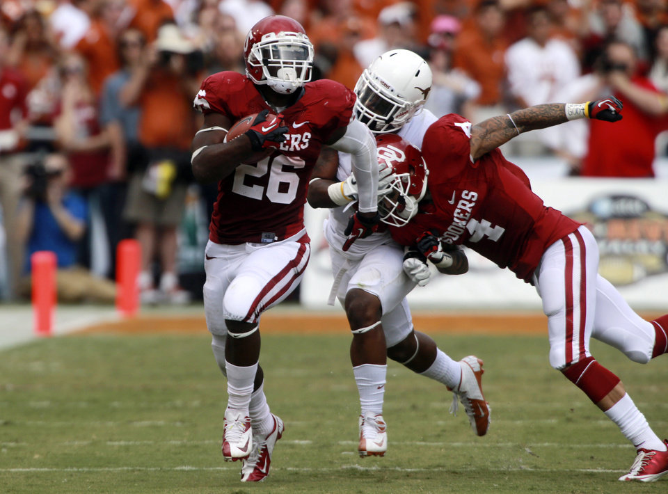 Photo -   Oklahoma running back Damien Williams (26) breaks away for a touchdown run as teammate Kenny Stills (4) blocks Texas cornerback Quandre Diggs (6) during the first half of an NCAA college football game at the Cotton Bowl Saturday, Oct. 13, 2012, in Dallas. (AP Photo/Michael Mulvey)