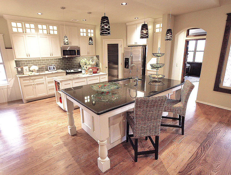 An island and hefty table leave plenty of room in the open kitchen of the McCaleb Homes model in the Arbor Creek addition in Edmond. <strong>David McDaniel - The Oklahoman</strong>