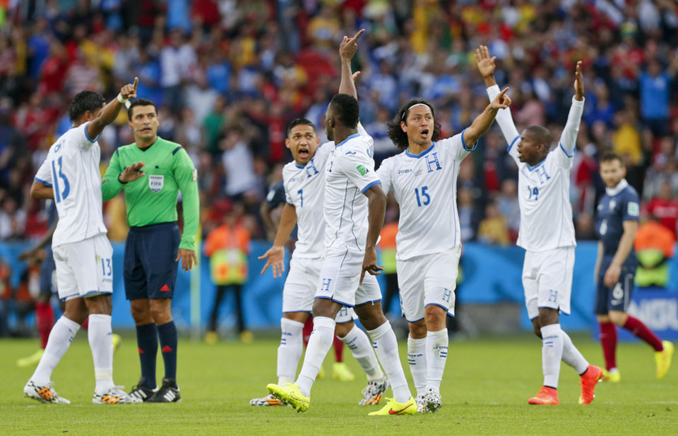 Photo - Honduras players complain to referee Sandro Ricci from Brazil after he awarded a goal to France using goal line technology during the group E World Cup soccer match between France and Honduras at the Estadio Beira-Rio in Porto Alegre, Brazil, Sunday, June 15, 2014.  (AP Photo/Jon Super)