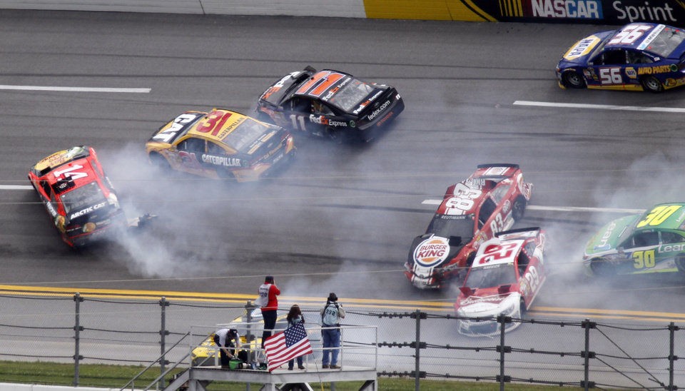 Photo - Cars spin through Turn 1 in a multi-car wreck during the NASCAR Sprint Cup Series Aaron's 499 auto race at Talladega Superspeedway in Talladega, Ala., Sunday, May 5, 2013. Tony Stewart (14), Jeff Burton (31), Brian Vickers (11), David Reutimann (83), Kevin Harvick (29), David Stremme (30) and Martin Truex Jr., all participate in the wreck. (AP Photo/Butch Dill)