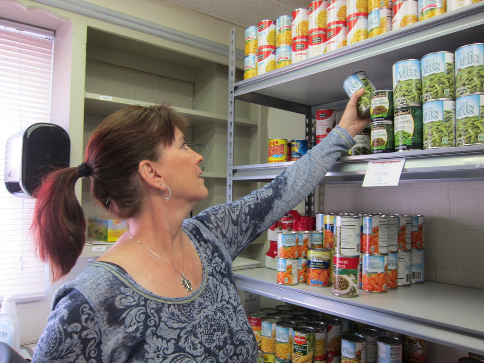 Photo -  Sandy Orchard, co-founder of No Boundaries International, stocks canned vegetables in the food pantry at the organization's Firehouse Community Center on South Robinson. Photo by Carla Hinton, The Oklahoman