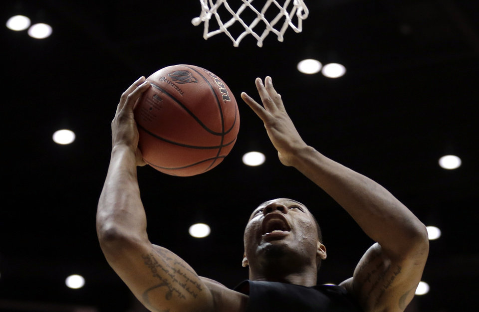 Photo - Oklahoma State guard Marcus Smart shoots during practice at the NCAA college basketball tournament Thursday, March 20, 2014, in San Diego. Oklahoma State faces Gonzaga in a second-round game on Friday. (AP Photo/Gregory Bull)