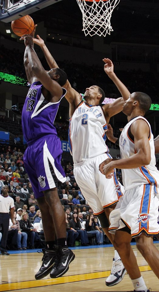 Sacramento's Tyreke Evans (13) tries for a rebound in front of Oklahoma City's Thabo Sefolosha (2) and Russell Westbrook (0) during the NBA preseason game between the Sacramento Kings and the Oklahoma City Thunder at the Ford Center in Oklahoma City, Thursday, Oct. 22, 2009. Photo by Nate Billings, The Oklahoman