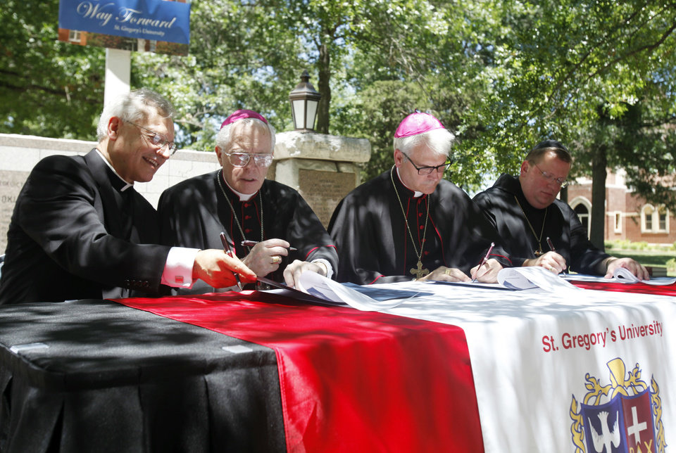 Photo - In a plaza outside St. Gregory's Abbey, St. Gregory's University and Catholic Church leaders in Oklahoma sign a memorandum of agreement Friday, June 28, 2013, establishing the Catholic Church as a major sponsor of the Shawnee university. From left are: the Rev. Don Wolf, St. Gregory's chairman of the board; Tulsa Bishop Edward Slattery; Archbishop of Oklahoma City Paul S. Coakley; and Abbot Lawrence Stasyszen with St. Gregory's.  Aliki Dyer - The Oklahoman