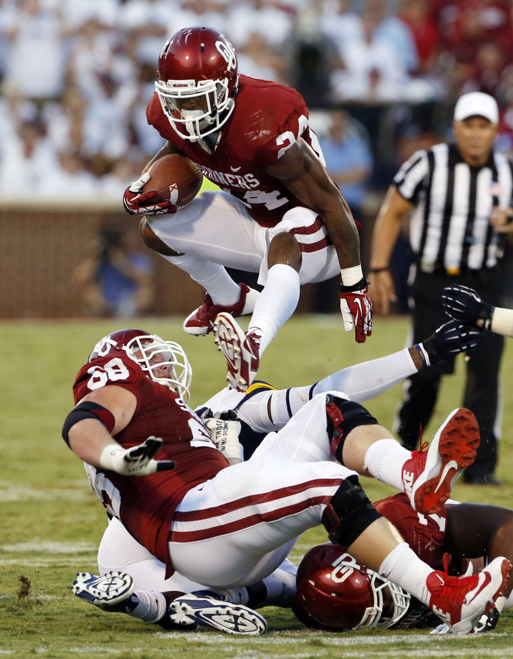 Photo - Oklahoma's Brennan Clay (24) carries during a college football game between the University of Oklahoma Sooners (OU) and the West Virginia University Mountaineers at Gaylord Family-Oklahoma Memorial Stadium in Norman, Okla., on Saturday, Sept. 7, 2013. Photo by Steve Sisney, The Oklahoman