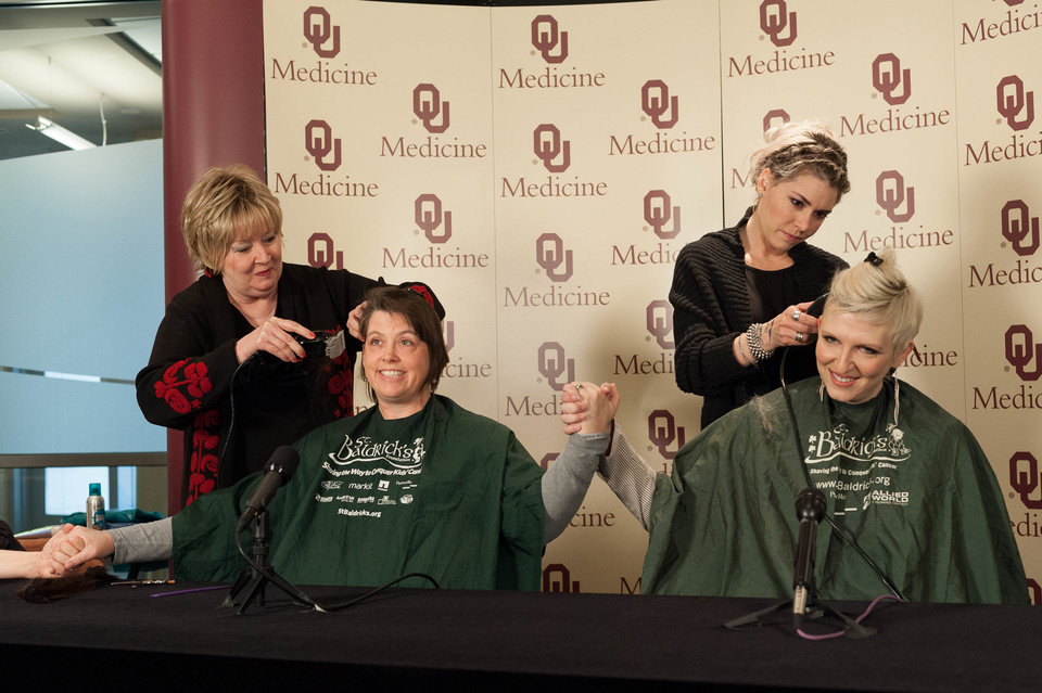 Cathy Rogers, with Heads Above Salon at the Stephenson Cancer Center, and Mary Timme, with Tonic the Salon, shave Dr. Rene McNall-Knapp and TeNeil Spaeth's heads Friday during a news conference. Photos provided by Brittany Johnson, OU Physicians