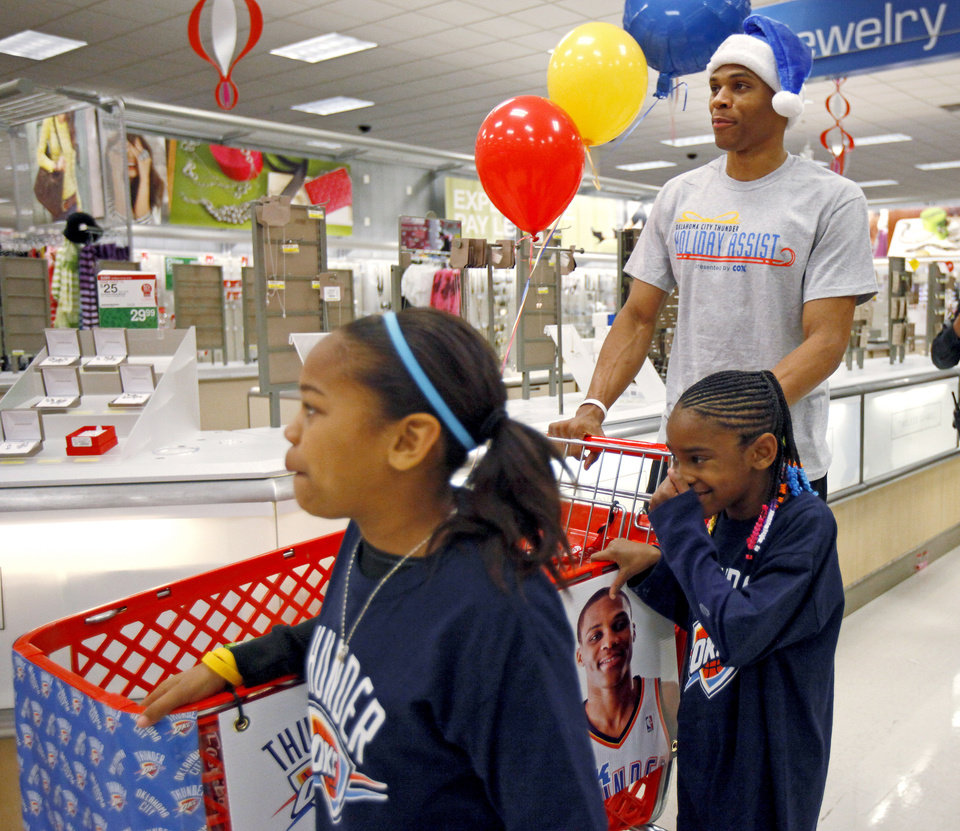 Photo - NBA BASKETBALL TEAM / CHILD / CHILDREN / KIDS / CHARITY: Russell Westbrook with the Oklahoma City Thunder shops with Destiny Williams, 10, left, and Jailin Williams, 7, during a shopping spree with the Sunbeam Family Services Grandparents Raising Grandkids program and the Thunder at a Target store in Oklahoma City, Thursday, December 16, 2010.  Photo by Bryan Terry, The Oklahoman ORG XMIT: KOD