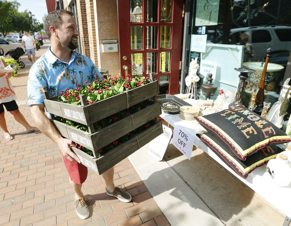 Photo -  Sterling's owner David Spannagel looks for a space to place more sale items outside his store. [PHOTO BY PAUL HELLSTERN, THE OKLAHOMAN]