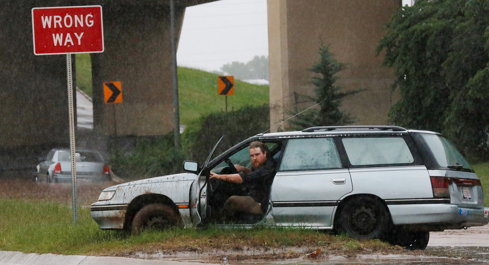Photo - A man opens his driver-side door after getting this car stuck in the mud in the median on the northbound I-235 ramp from NW 23 Street. Brief periods of heavy rain caused road flooding and created hazardous driving conditions around 7 pm Saturday, May 23, 2015.  Oklahoma City police used their vehicles to barricade all directions of traffic at NW 23 and Broadway, preventing vehicles from driving into high and rushing water. Photo by Jim Beckel, The Oklahoman.
