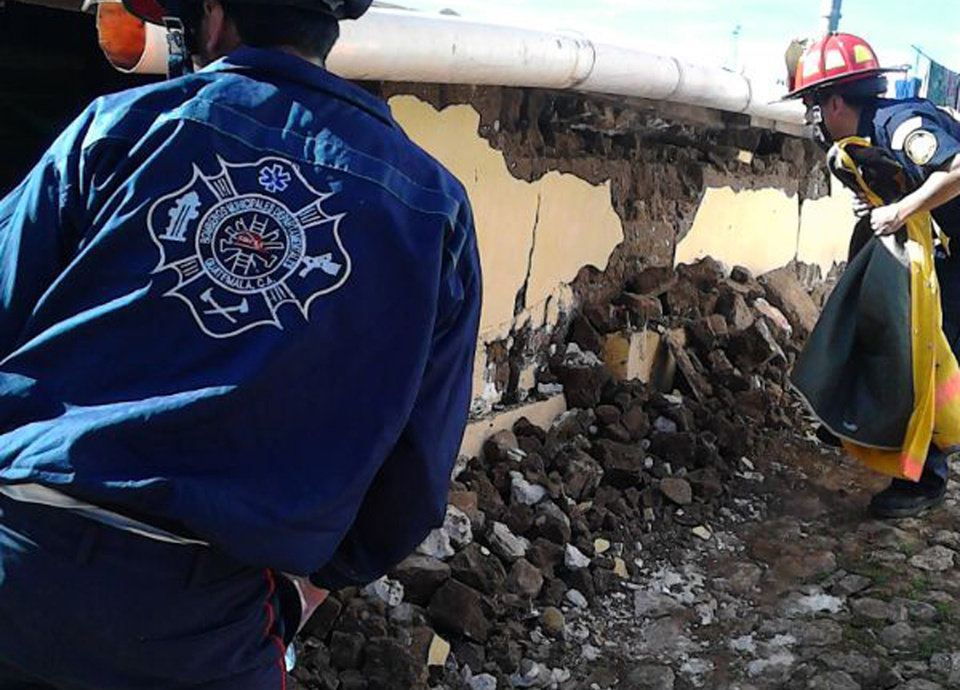Photo - In this photo released by Bomberos Departamentales, or regional firefighters, firefighters check a home that collapsed during an earthquake in San Pedro, Guatemala, Monday, July 7, 2014. A magnitude-6.9 earthquake on the Pacific Coast jolted a wide area of southern Mexico and Central America Monday. (AP Photo/Bomberos Departamentales)