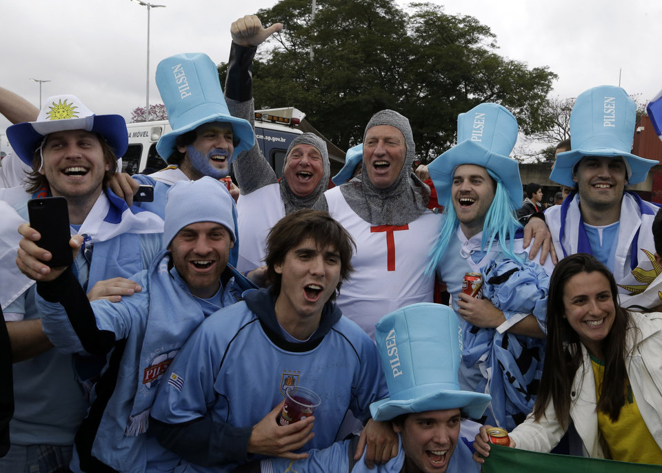 Photo - Fans of England and Uruguay cheer for their national teams outside the Itaquerao Stadium before the group D World Cup soccer match between Uruguay and England in Sao Paulo, Brazil, Thursday, June 19, 2014. (AP Photo/Thanassis Stavrakis)