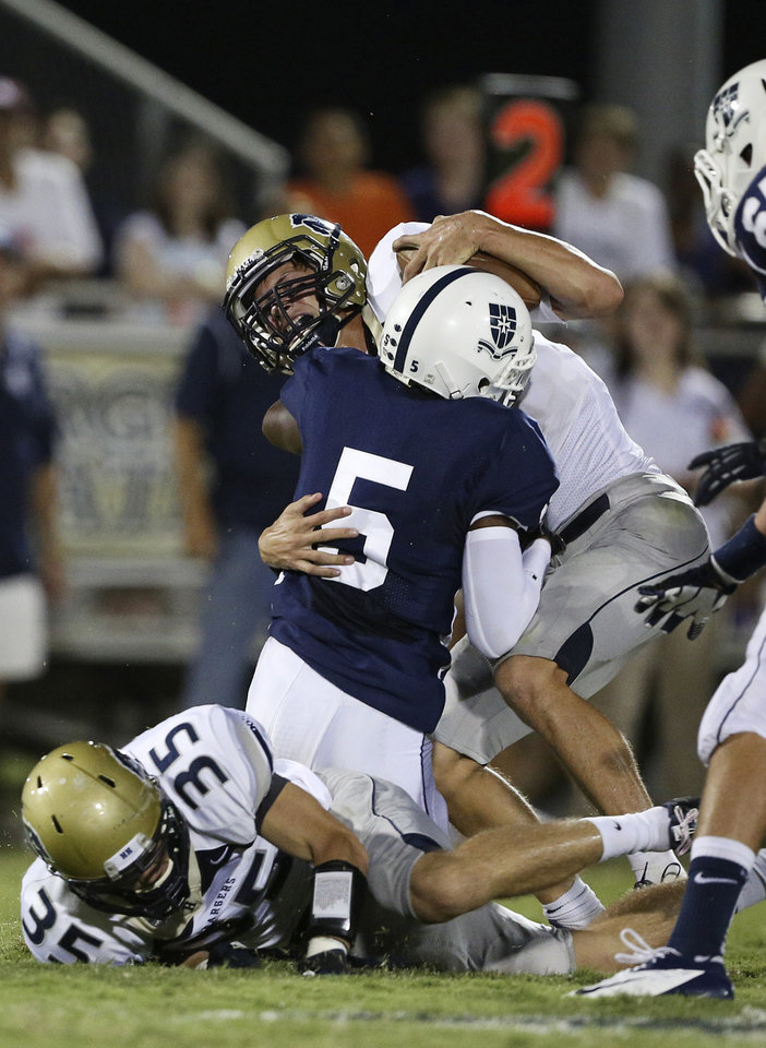 Photo - Heritage Hall's Connor McGinnis (4) is taken down by Casady's Gary Woods (5) during a game at Casady High School in The Village, Okla., Thursday, Aug. 30, 2012.  Photo by Garett Fisbeck, The Oklahoman