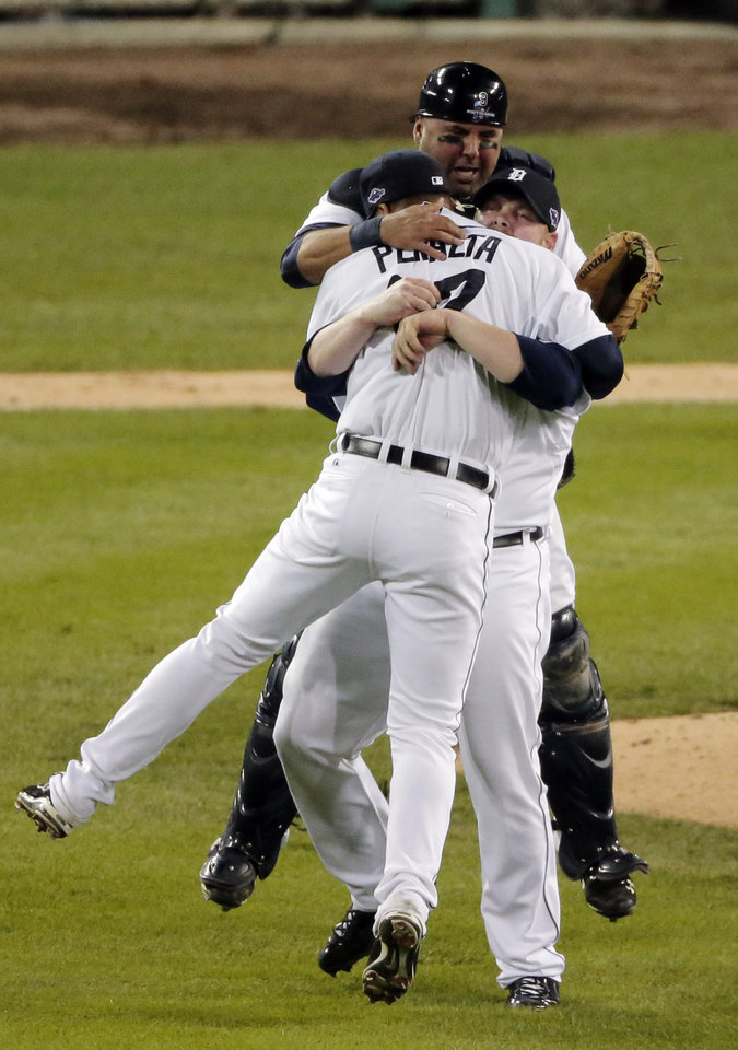 Photo -   Detroit Tigers' Gerald Laird, rear, Phil Coke, center and Jhonny Peralta (27)celebrate after winning Game 4 of the American League championship series against the New York Yankees Thursday, Oct. 18, 2012, in Detroit. The Tigers move on to the World Series. (AP Photo/Charlie Riedel)