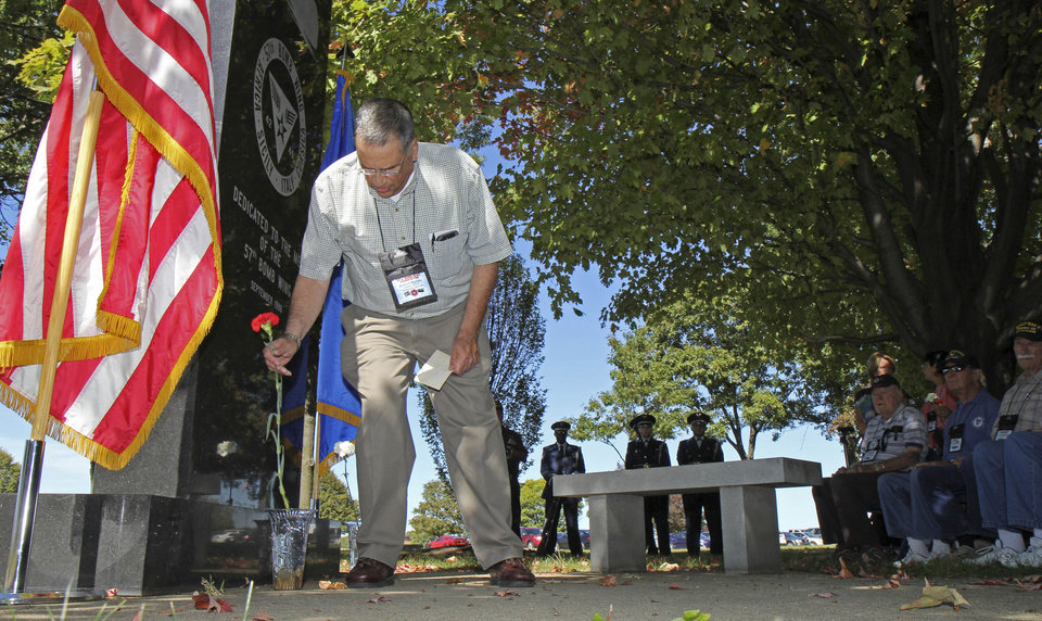 Photo - In this Sept. 27, 2013 photo, Bob Marino, whose father was a World War II veteran in the 57th Bomb Wing, places a flower at the memorial to the 57th Bomb Wing as he takes part in a memorial ceremony during a reunion outside the U.S. Air Force Museum at Wright Patterson Air Force base in Dayton, Ohio. Marino, 72, a retired IRS attorney from Basking Ridge, N.J., helped organize the gathering. His Brooklyn-native father, Capt. Benjamin Marino, died in 1967 and left numerous photos from the war, and Marino set about trying to identify and organize them. To learn more about his father's experiences, he corresponded with other veterans. (AP Photo/Tom Uhlman)