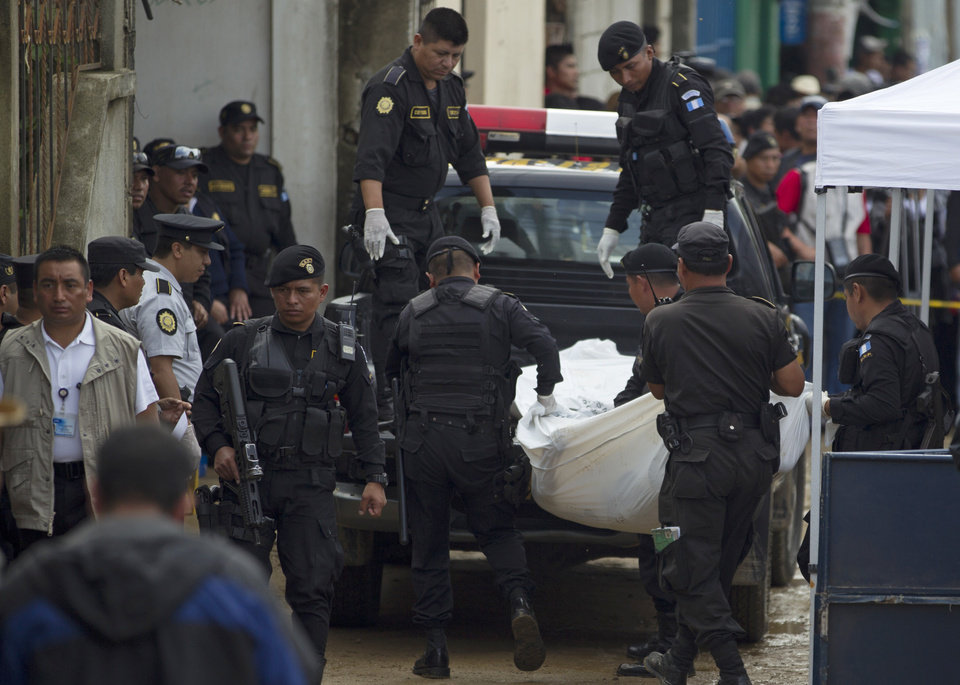 Photo - Bodies are taken away by police after an attack in San Jose Nacahuil, on the outskirts of Guatemala City, Sunday, Sept. 8, 2013. Men firing from a car poured gunshots into three cantinas in this rural town, killing at least 10 people and injuring 19, local firefighters said Sunday. (AP Photo/Moises Castillo)