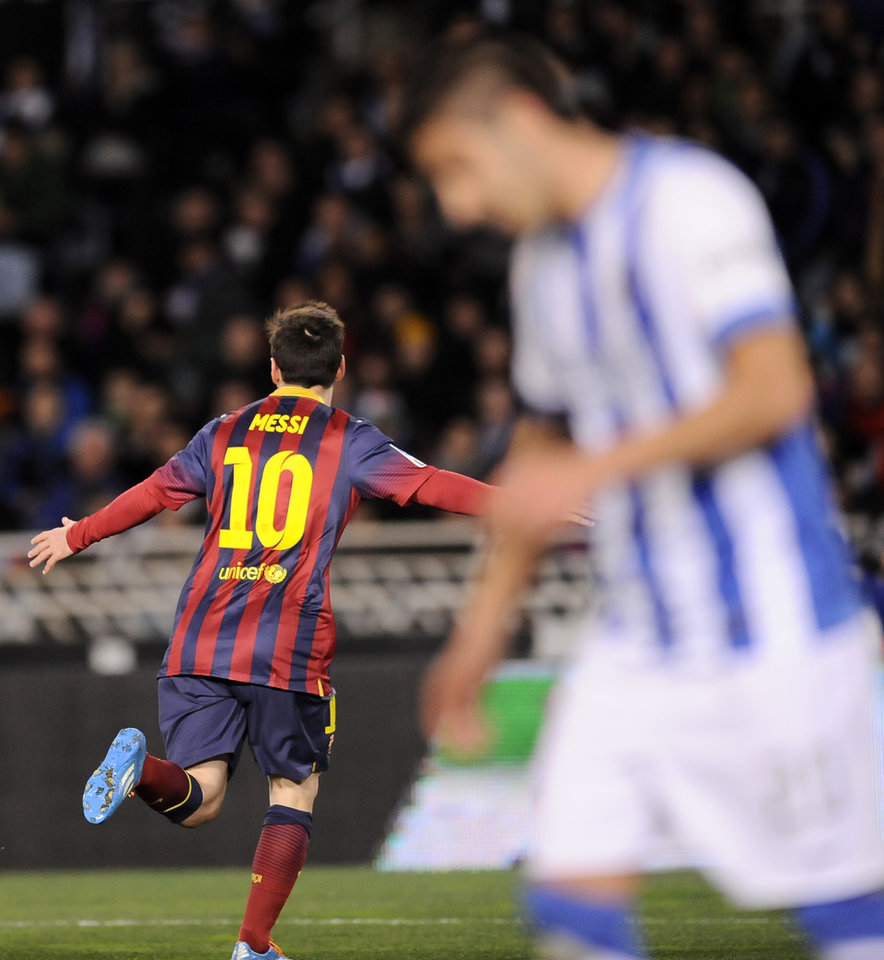 Photo - FC Barcelona's Lionel Messi of Argentina left, celebrates after scoring his goal against Real Sociedad, during their Spanish Copa del Rey semifinal second leg soccer match, at Anoeta stadium, in San Sebastian northern Spain, Wednesday, Feb. 12, 2014. (AP Photo/Alvaro Barrientos)