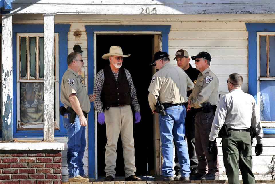 Photo - Agents from the Oklahoma State Bureau of Investigation and Washita County sheriff's deputies talk on the front porch of a house in the 200 block of S 4 in Sentinel.  Photos by Jim Beckel, The Oklahoman  Jim Beckel -  THE OKLAHOMAN
