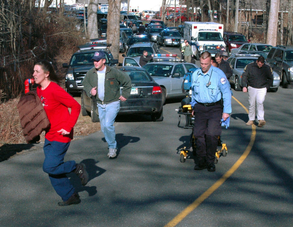 Photo - FILE - In this Dec. 14, 2012 file photo provided by the Newtown Bee, paramedics and others rush toward Sandy Hook Elementary School in Newtown, Conn., shortly after Adam Lanza opened fire, killing 26 people, including 20 children. While the people of Newtown do their best to cope with loss and preserve the memories of their loved ones, another class of residents is also finding it difficult to move on: the emergency responders who saw firsthand the terrible aftermath of last week's school shooting. (AP Photo/Newtown Bee, Shannon Hicks, File) MANDATORY CREDIT: NEWTOWN BEE, SHANNON HICKS