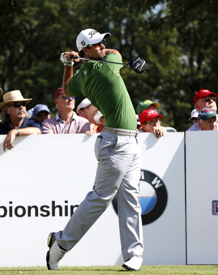 Photo - Adam Scott watches his tee shot on the 10th hole during the first round of the BMW Championship golf tournament at Conway Farms Golf Club in Lake Forest, Ill., Thursday, Sept. 12, 2013. (AP Photo/Charles Rex Arbogast)