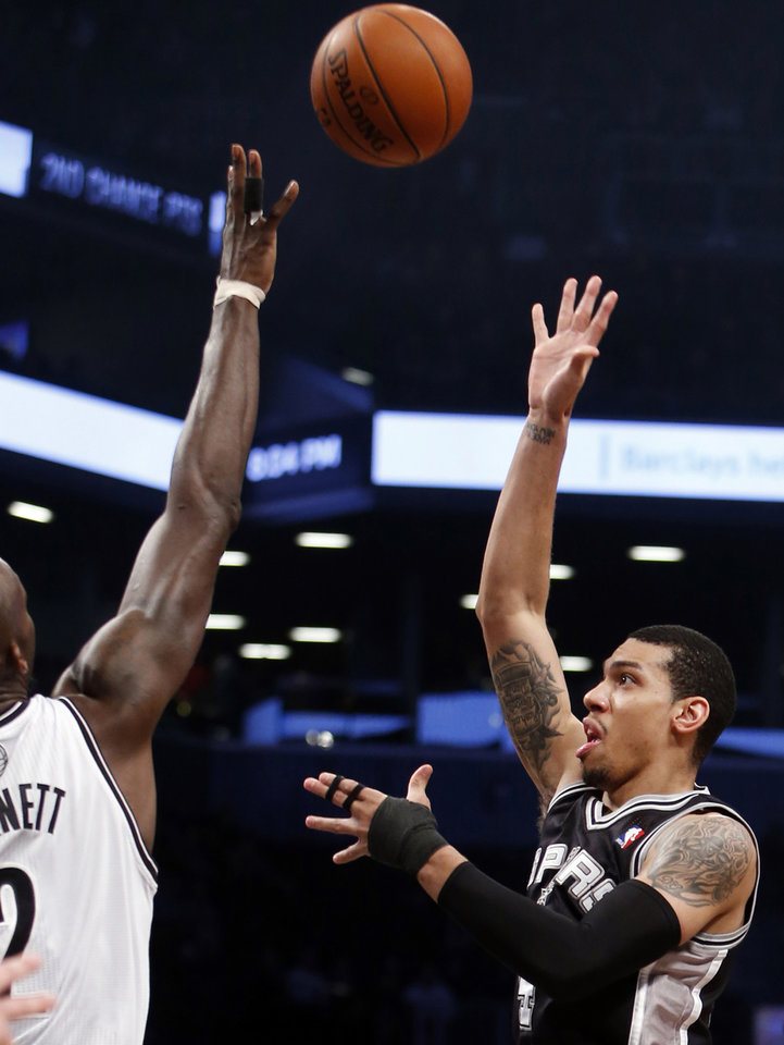 Photo - San Antonio Spurs' Danny Green, right, shoots against Brooklyn Nets' Kevin Garnett during the first half of an NBA basketball game on Thursday, Feb. 6, 2014, in New York. (AP Photo/Jason DeCrow)