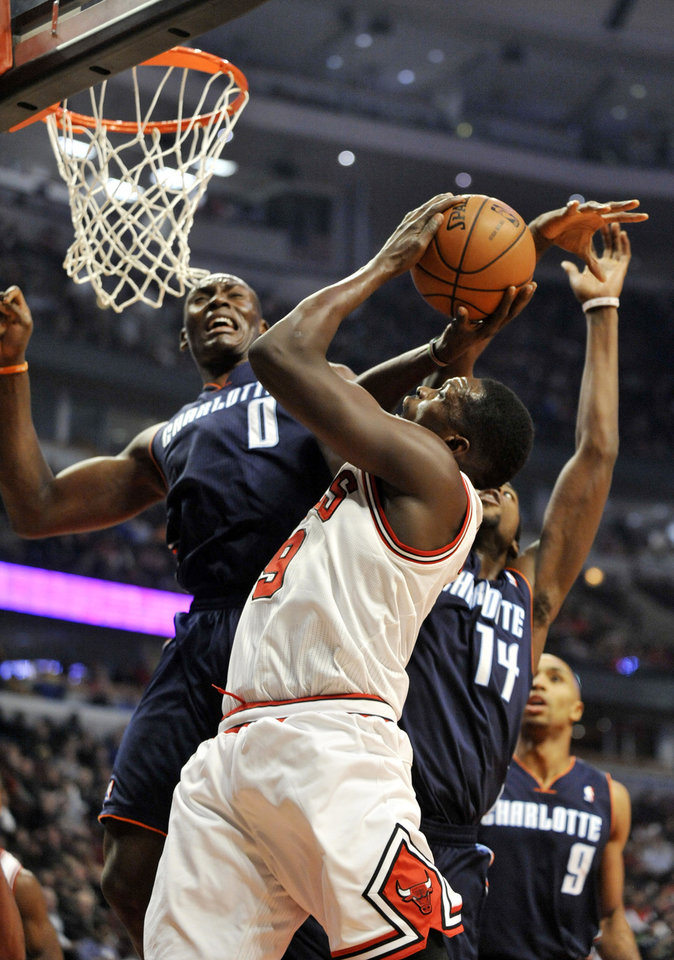 Photo - Chicago Bulls' Luol Deng (9), of South Sudan goes up for a shot against Charlotte Bobcats' Bismack Biyombo (0), of Congo, and Michael Kidd-Gilchrist (14), during the first quarter of an MLB basketball game in Chicago, Monday, Nov. 18, 2013. (AP Photo/Paul Beaty)