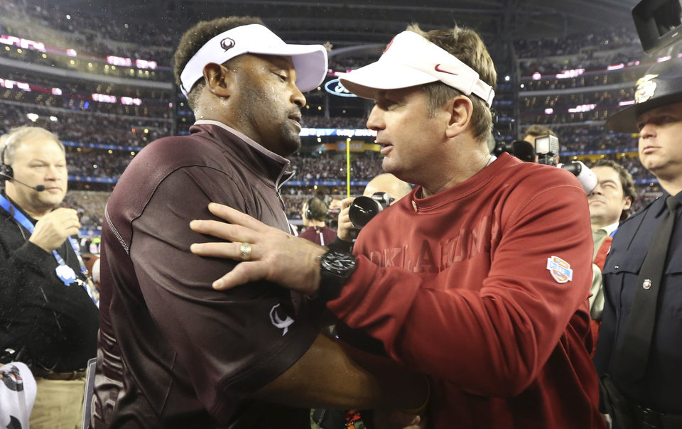 Photo - Texas A&M head coach Kevin Sumlin, left, and Oklahoma head coach Bob Stoops shake hands after the Cotton Bowl NCAA college football game Friday, Jan. 4, 2013, in Irving, Texas. Texas A&M  won 41-13. (AP Photo/LM Otero)